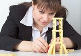 Ung flicka i svart koncentrerad bygger torn av — Stockfoto