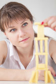 Young girl concentrated builds on table tower of — Stock Photo
