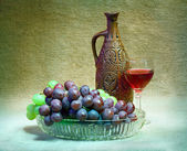 Still-life from grapes, bottle and glass of wine — Stock Photo