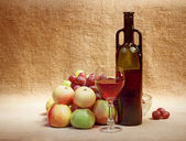 Wine and fruit against brown sacking — Stock Photo