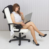 Beautiful sexy girl sits in an armchair — Stock Photo