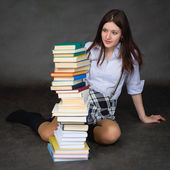 Schoolgirl with amazement looks at books — Stock Photo