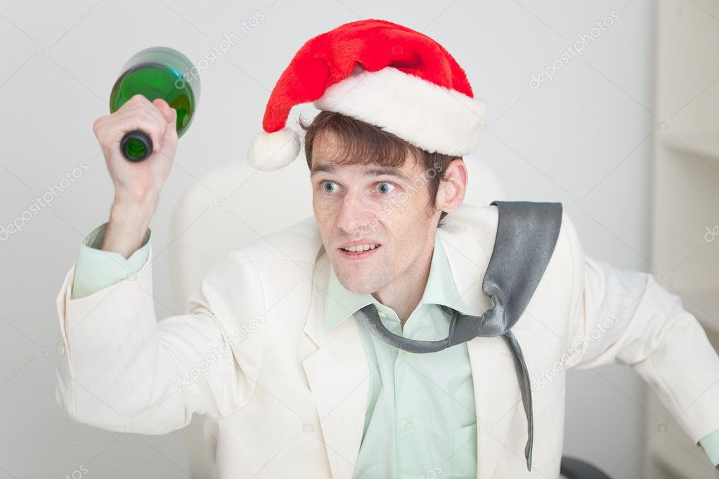 The young guy in a white jacket and a christmas hat brawls with a bottle in a hand — Stock Photo #2315696