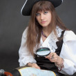Royalty-Free Stock Photo: Woman - sea pirate with a map and magnifier