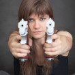Serious woman aims from two pistols — Stock Photo