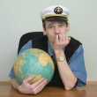 Man in a sea cap of captain with globe — Stock Photo