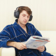 Man in ear-phones on sofa reads journal — Stock Photo #2326432