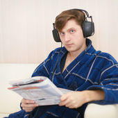 Person in big ear-phones on sofa reads newspaper — Stock Photo