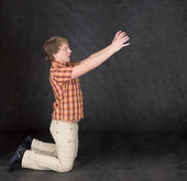 Amusing man is kneeling, stretch hands — Photo