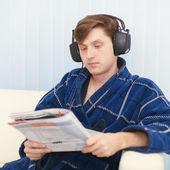 Man in big ear-phones on sofa reads newspaper — Стоковое фото