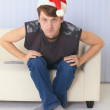 Royalty-Free Stock Photo: Young man in Christmas cap sits on sofa and watc