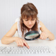 Girl with poor eyesight works with computer keyb - Stock Photo