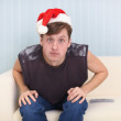 Man sits on sofa in Christmas cap — Stock Photo #2331265