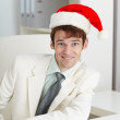 Happy man in Christmas cap at office — Stock Photo