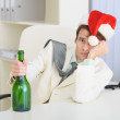 Young drunkard celebrates Christmas with wine bo — Stock Photo