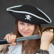 Young woman pirate gets a sabre from sheath — Stock Photo