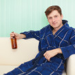 Young man drinks beer on sofa — Stock Photo #2336020