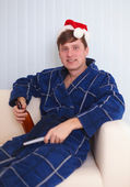 Person in red santa s cap sits on sofa — Stock Photo