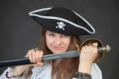 Young woman pirate gets a sabre from sheath — Stock fotografie