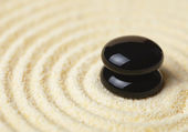 Two black stones put in a pile on sand — Stock Photo