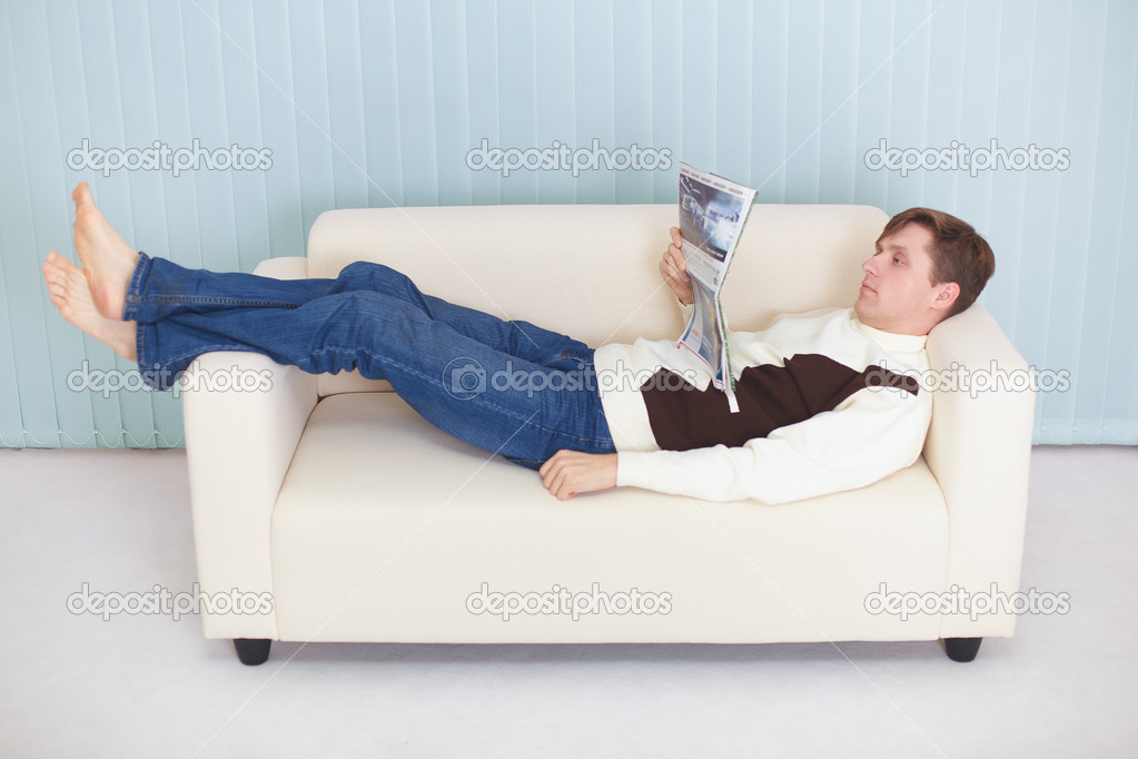 The young man reads magazine lying on a couch  Stock Photo #2334975