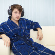 Royalty-Free Stock Photo: Man in dark blue dressing gown listens to music