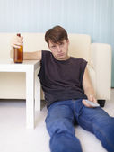 Drunk man sits on floor at TV — Stock Photo
