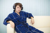 Man in dark blue dressing gown listens to music — Stock Photo