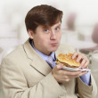Young funny businessman eats a hamburger - Stock Photo