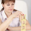 Stock Photo: Girl builds precarious tower of dominoes