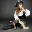 Girl pirate, map with magnifying glass — Stock Photo