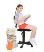Schoolgirl near big pile of textbooks — Stock Photo