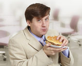 Young funny businessman eats a hamburger — Stock Photo