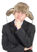 Young man in a fur hat dreams on white backgroun — Stock Photo