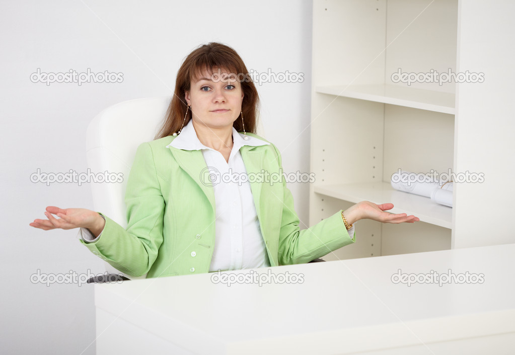 A woman sitting at a table alone and upset a helpless gesture  Stock Photo #2356890