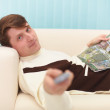 Smiling man, lying on couch with TV — Stock Photo #2363842