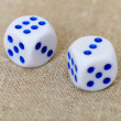 Two dice on coarse linen — Stock Photo