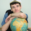 Man in a captain's cap with globe — Stock Photo