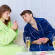 Couple sitting on couch, playing cards — Stock Photo