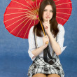 Royalty-Free Stock Photo: Girl with red oriental umbrella on blue