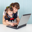 Mom teaches daughter to use laptop — Stock Photo