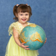 Beautiful little girl with globe — Stock Photo