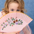 Girl coyly covered face with fan — Stock Photo