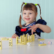 Stock Photo: Cheerful child playing with small toys