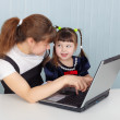 Mother and daughter playing with laptop — Stock Photo
