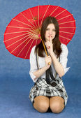 Girl with red oriental umbrella on blue — Stock Photo