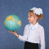 Schoolgirl looking at a globe — Stok fotoğraf