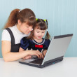 Stock Photo: Mother teaches child to use laptop