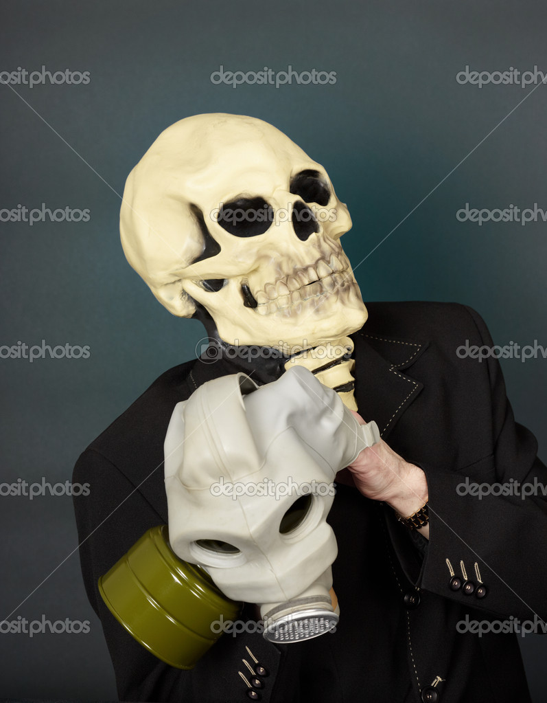 Man in a mask of death in a hurry to wear a gas mask — Stock Photo #2386000