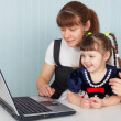 Mother and daughter sitting at table with laptop — Stock Photo